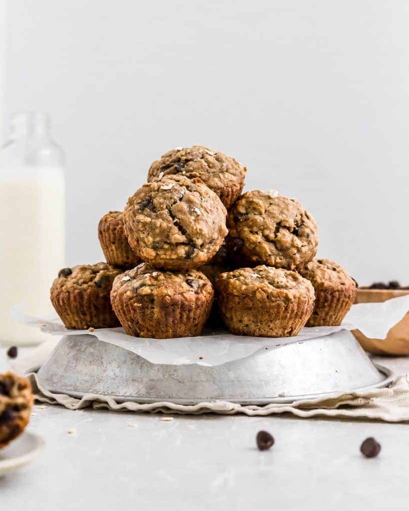 A big pile of healthy banana chocolate chip muffins with a glass of plant milk.