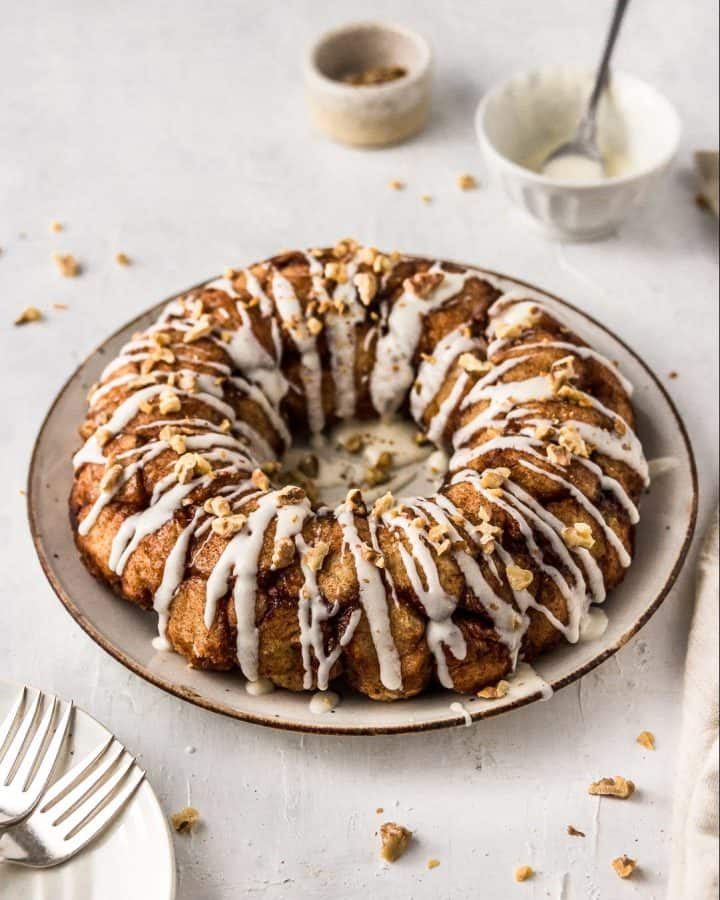 1-Hour Vegan Monkey Bread Bundt (No-Rise) on a plate drizzled with icing and topped with toasted walnuts.