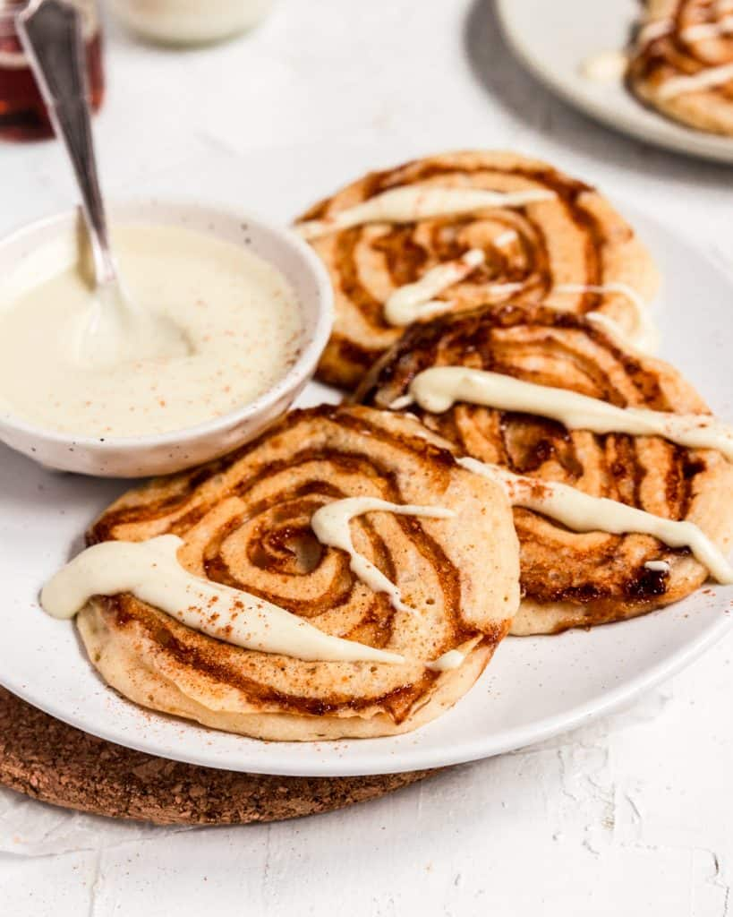 A plate of vegan cinnamon roll pancakes with healthy vegan cream cheese icing.