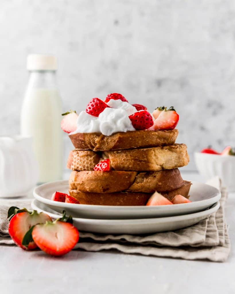 A stack of easy vegan french toast topped with coconut whipped cream and strawberries.
