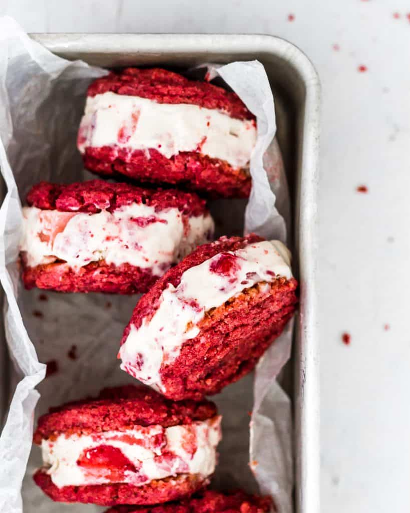 Red velvet ice cream sandwiches lined up in a baking dish.