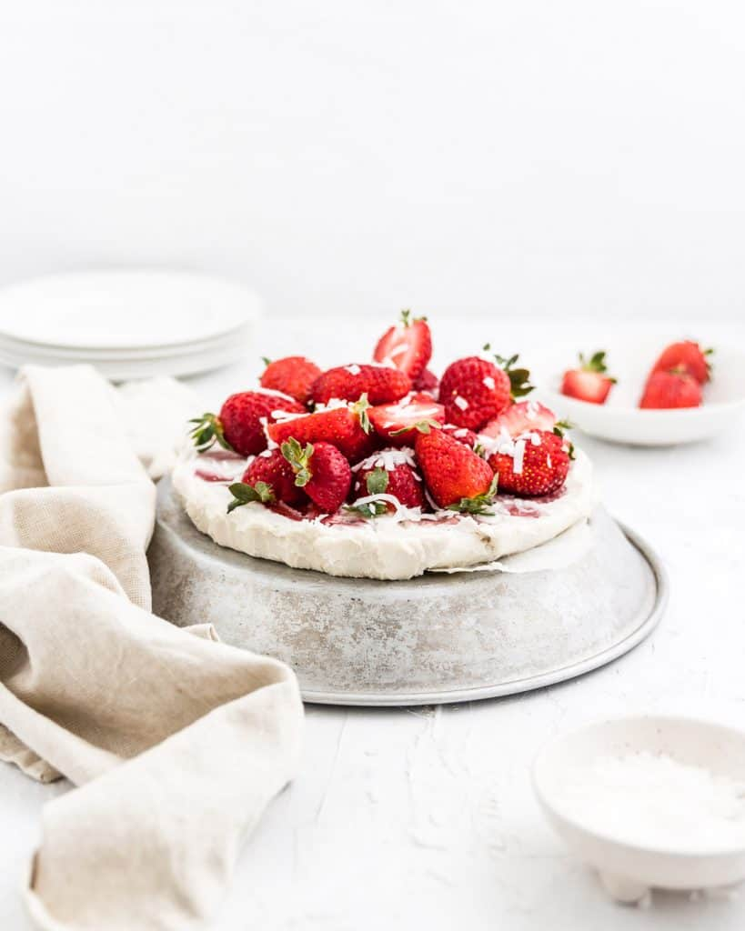 Vegan strawberry coconut ice cream cake with fresh strawberries and coconut shreds on top.