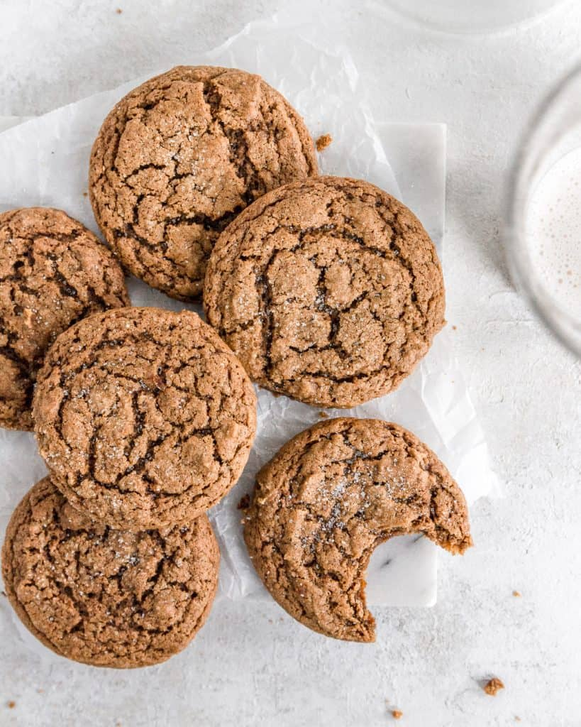 A small batch of chewy vegan ginger molasses cookies with a bite in one.