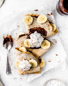 3 vegan spelt flour crepes topped with chocolate sauce, banana slices and coconut whipped cream.