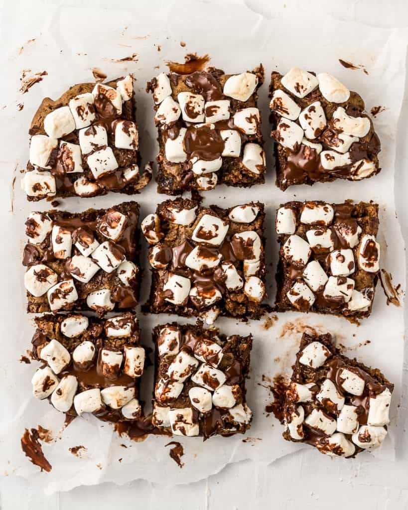 Batch of vegan and oil-free s'mores cookie bar with melted chocolate and mini vegan marshmallows sliced into 9 equal bars.