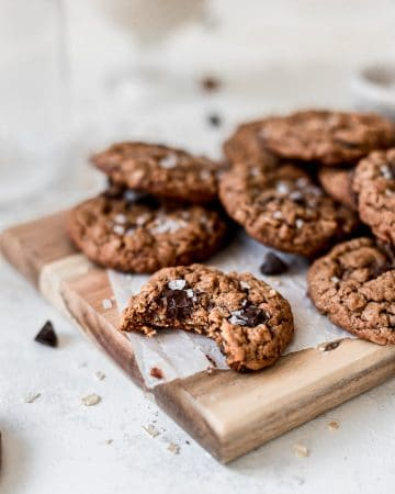 Bite shot of Vegan Oatmeal Chocolate Chip Cookies on a cutting board.