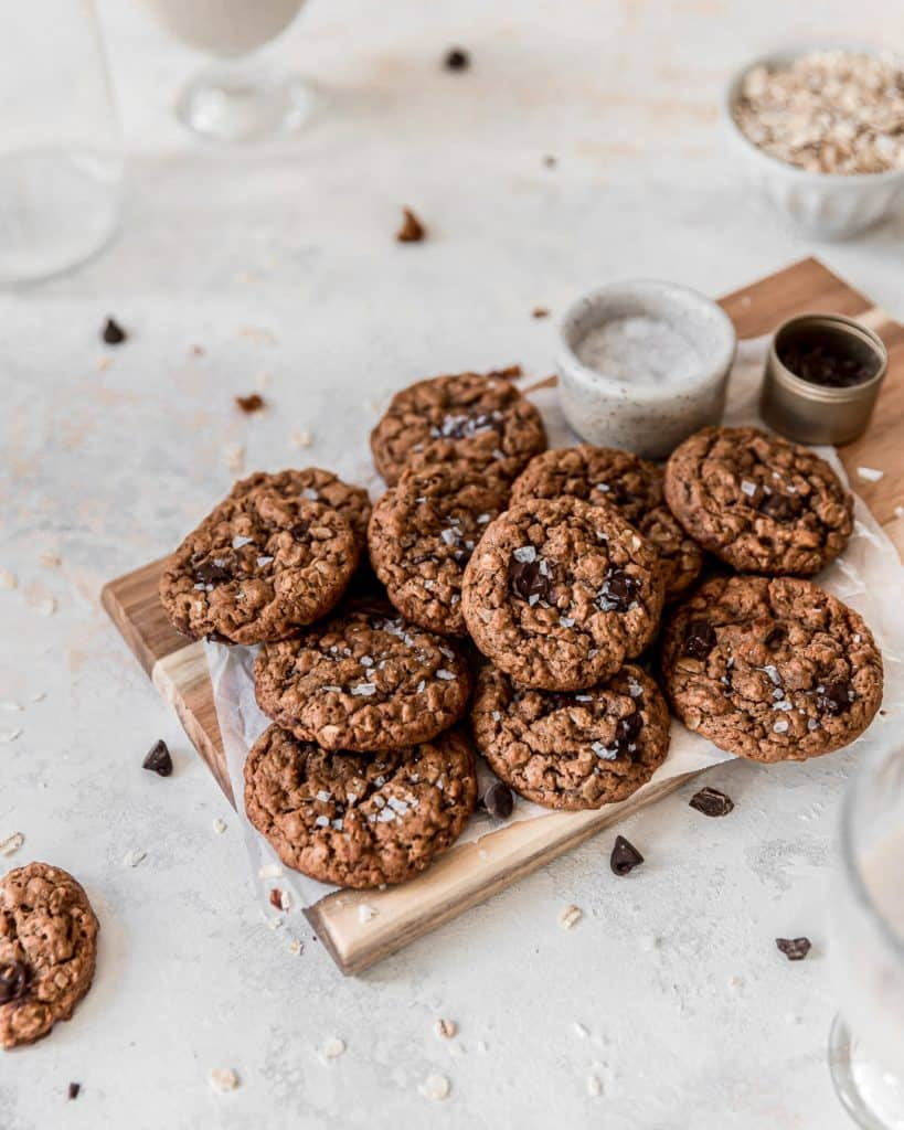 Pile of Vegan Oatmeal Chocolate Chip Cookies on a cutting board.