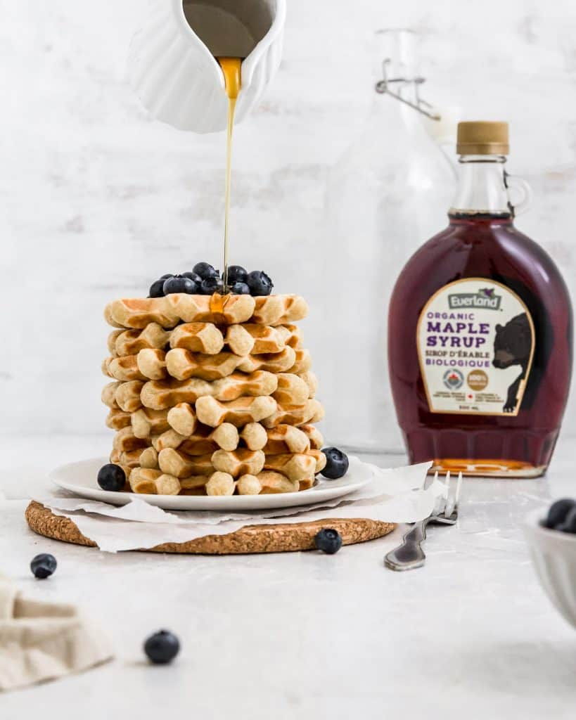 A stack of waffles with blueberries on top and a maple syrup drizzle.